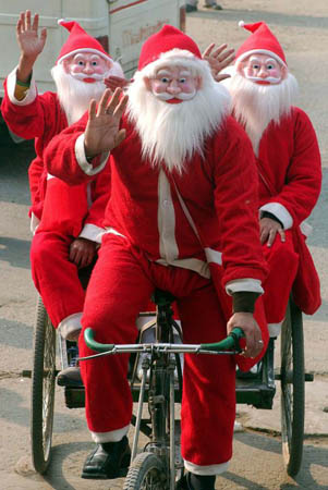 Men dressed as Santa Claus sit on a cycle-rickshaw
