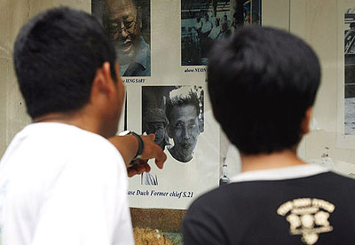 Tourists look at a portrait of Kaing Guek Eav, also known as Duch, the former head of the Khmer Rouge's S-21 prison, at Toul Sleng high school in Phnom Penh, Cambodia.
