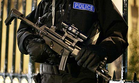 An armed British police officer stands guard on Whitehall in London