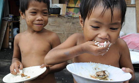 Filipino children eat rice, a staple crop that is under pressure across the developing world
