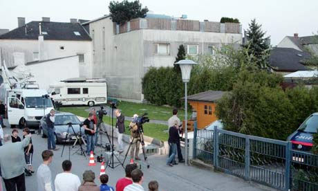 People watch at the back of a house where a 73-year-old man allegedly locked up his daughter in a basement for 24 years and fathered seven children with her, in Amstetten, Austria