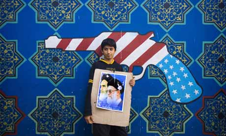 School boy in front of an anti-US mural in Iran