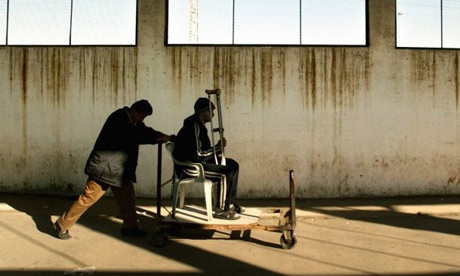 A porter pushes a 15-year-old Palestinian cancer patient through the Erez crossing between the Gaza Strip and Israel